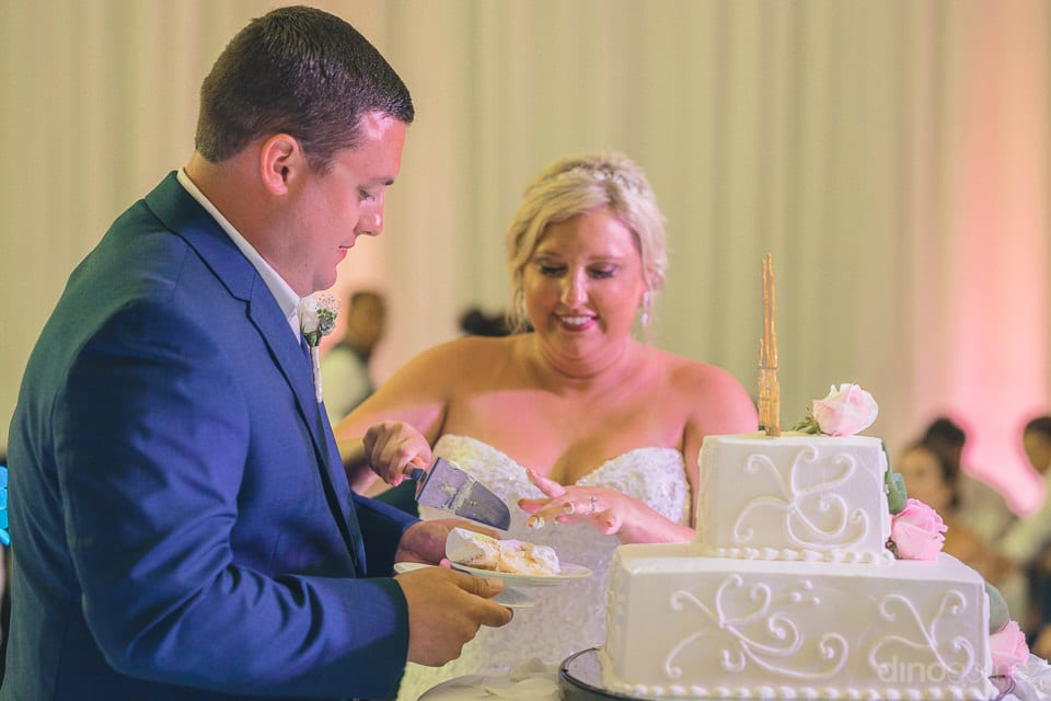 Lovely couple is cutting their beautiful 2-tier cake with beautiful smiles on their faces- Shannon & Jordan