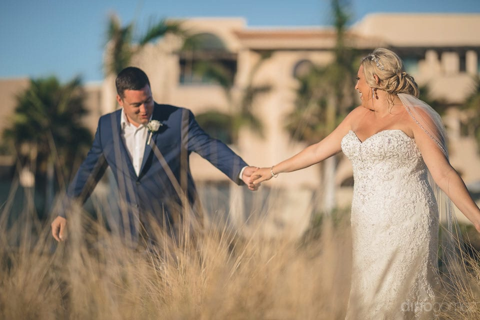 Beautiful couple is holding hands and walking through the golden bushes under the beautiful sky- Shannon & Jordan