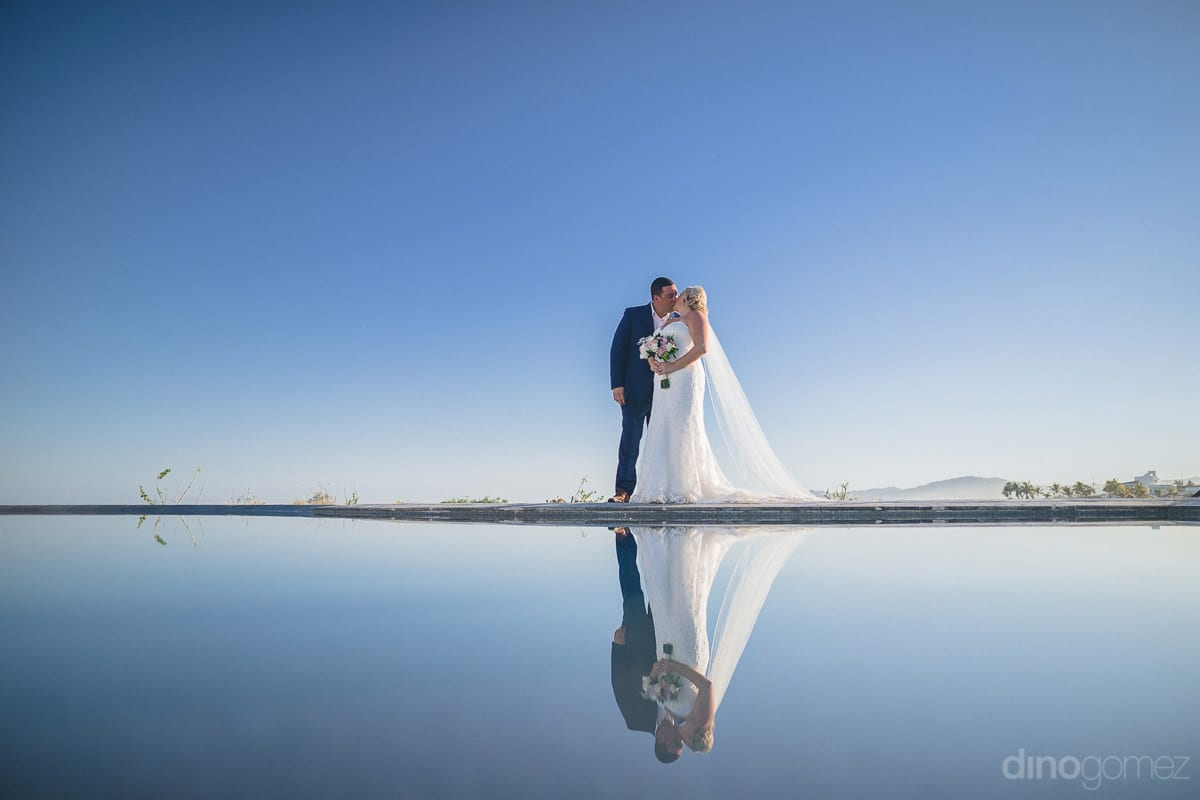 A unique picture of the couple standing at a hard surface is kissing each other while posing for the camera- Shannon & Jordan