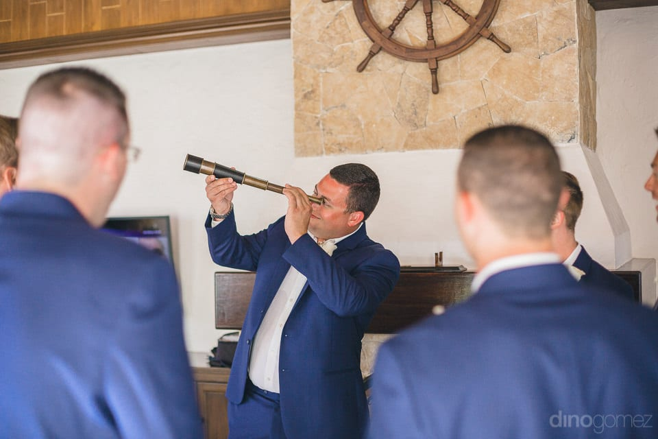 Groom is looking at something via an antique binoculars kept inside the palace along with his friends before the wedding- Shannon & Jordan