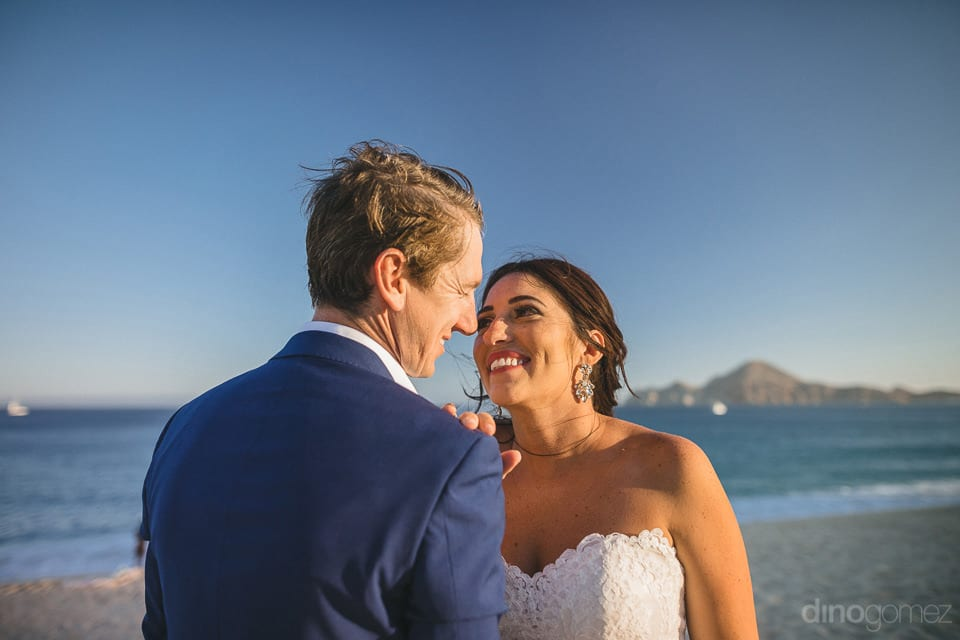Stunning couple smiling at each other on the beach-side- Aubrey & Chris