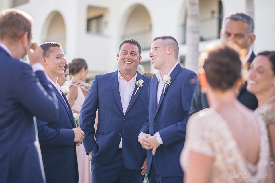 The groom is standing in a relaxed mood while talking and laughing with the family and friends during the wedding of lovely couple- Shannon & Jordan