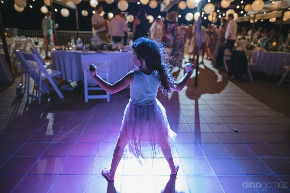 Little girl dancing at the floor under the LED lightings at the evening party of the newly married couple- Aubrey & Chris