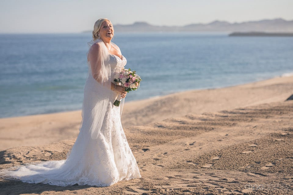 Lovely bride is standing on the sandy beach holding her wedding bouquet and posing for the camera- Shannon & Jordan