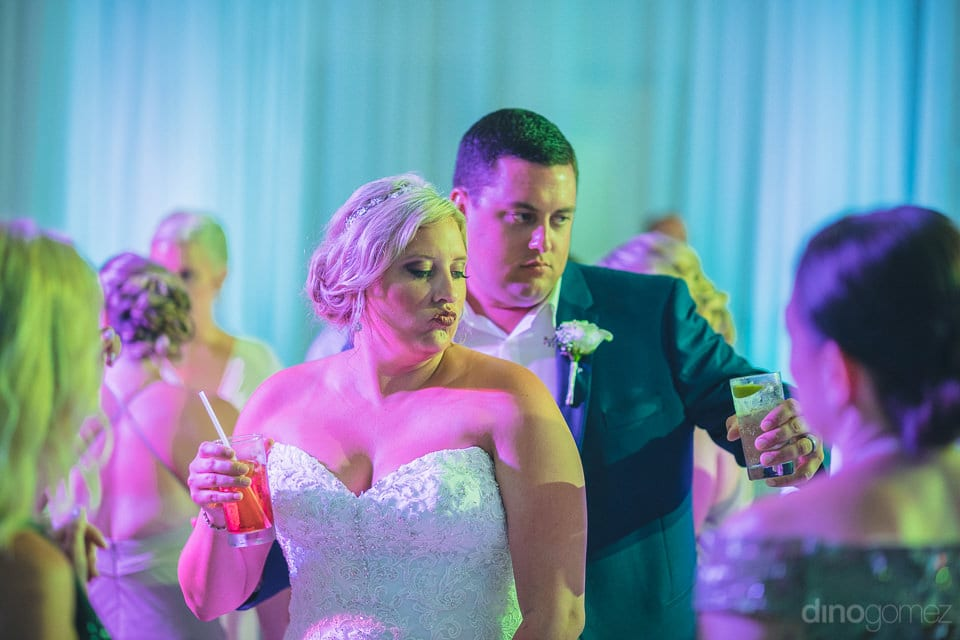 Lovely couple is holding glasses of drinks and dancing on the beats of music at the evening party- Shannon & Jordan