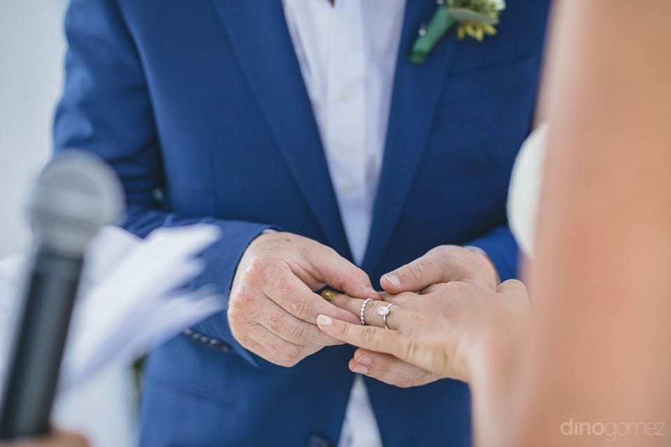 The groom can be seen making the bride wear a big and beautiful solitare wedding ring- Aubrey & Chris