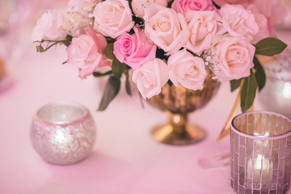 Beautiful pink and white roses are kept in the vase to enhance the overall look of the dinning table- Shannon & Jordan