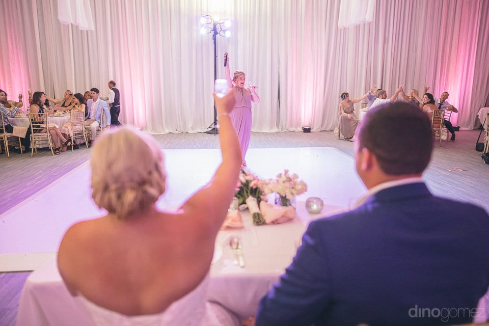 One of the couples friends is standing in the centre of the stage and raising a toast to the newly married couple- Shannon & Jordan