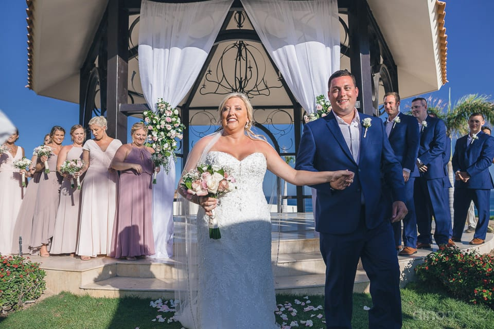 Beautiful newly married couple holding each others hands and bidding farewell to the guests after getting married- Shannon & Jordan