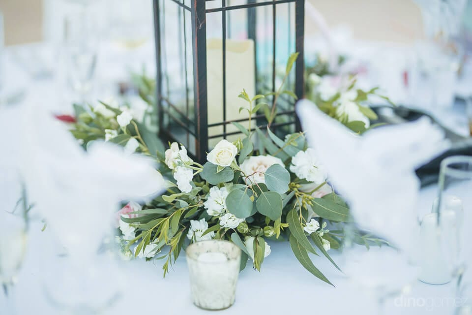 A glass candle placed in the centre of the table decorated with pink and white flowers- Aubrey & Chris