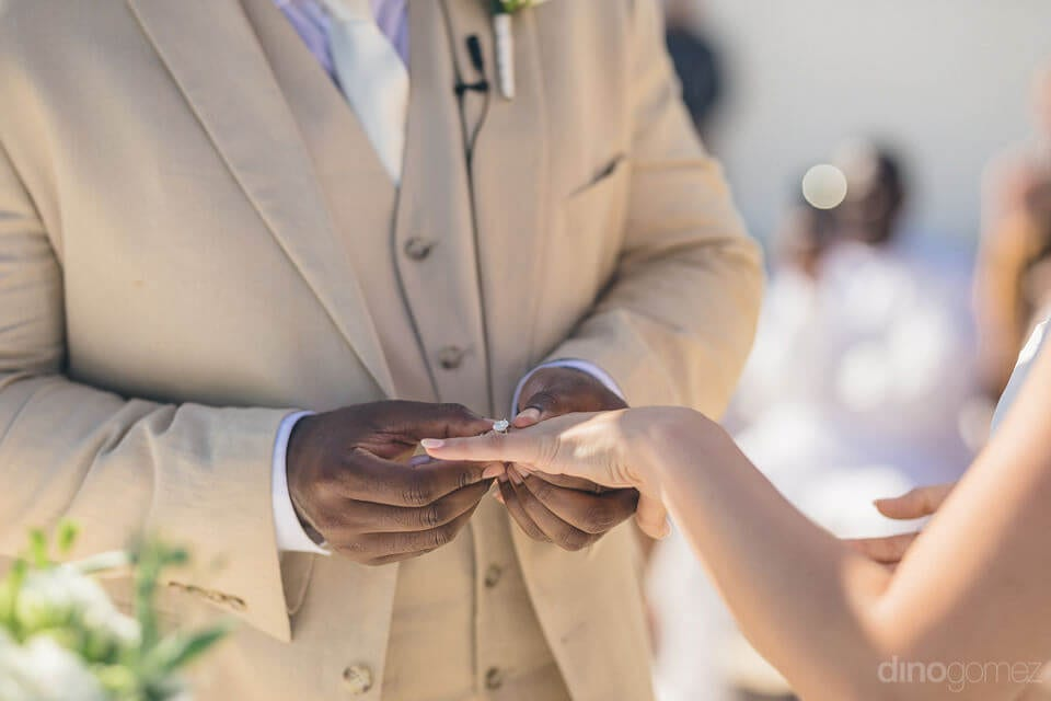 The picture captures the moment when the groom is gifting wedding ring to the lovely bride- Amber & Josh