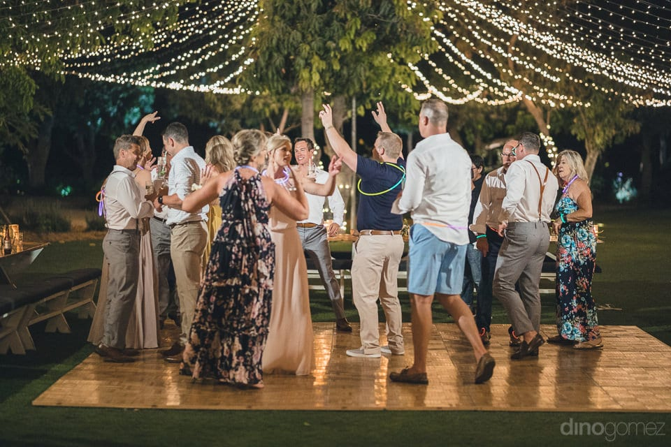 All the guests are happily dancing on the dance floor while wearing the glowbands under the moon and stars- Heather & Ross