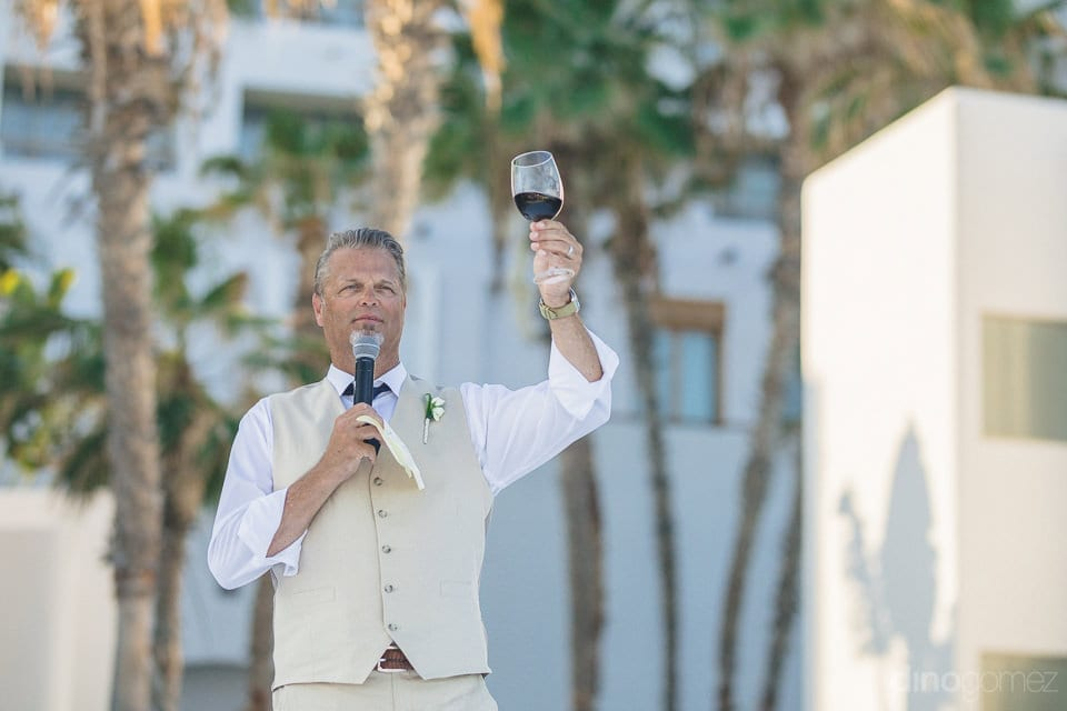 A gentleman is holding a mike in his one and and raising a toast holding the glass in another hand during the evening party of the couple- Amber & Josh