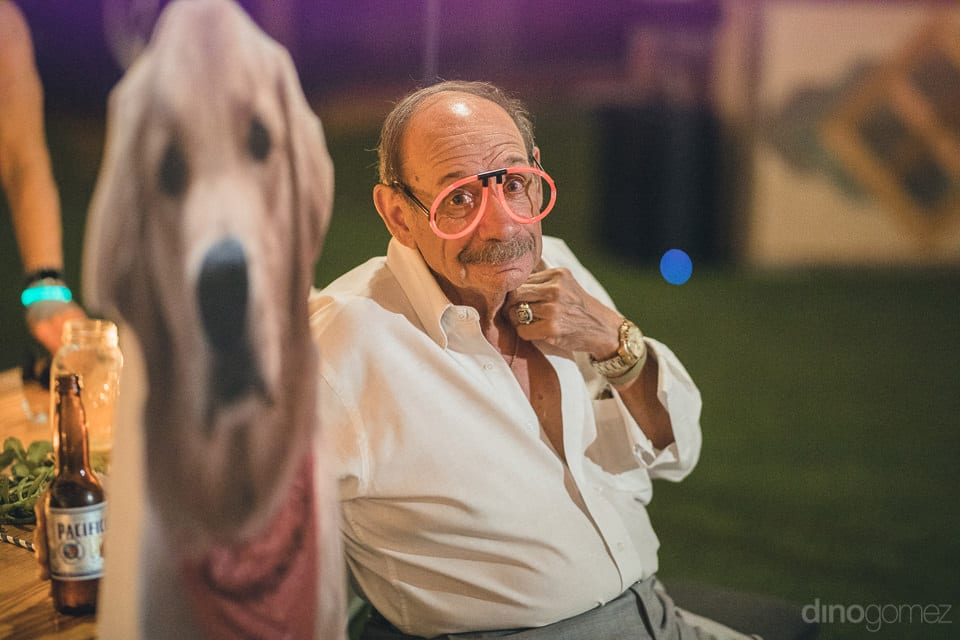 A handsome elderly man is sitting on the chair next to the hoarding of cute golden retriever dog during the evening party of the couple- Heather & Ross