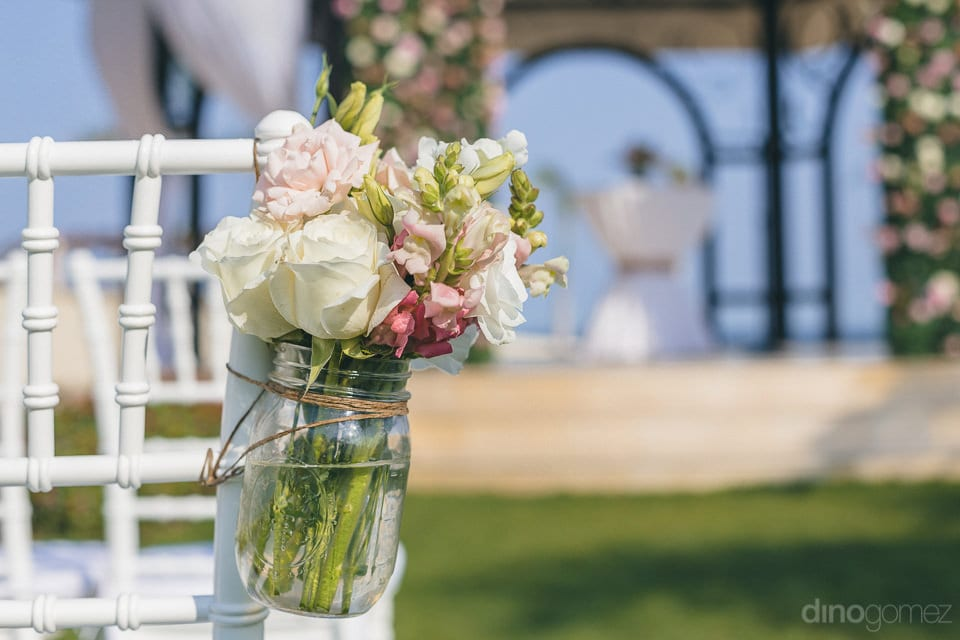 A cute little glass vase is tied to the chair containing beautiful roses for enhancing the loodk of the wedding venue of the lovely couple-  Jay & Drew