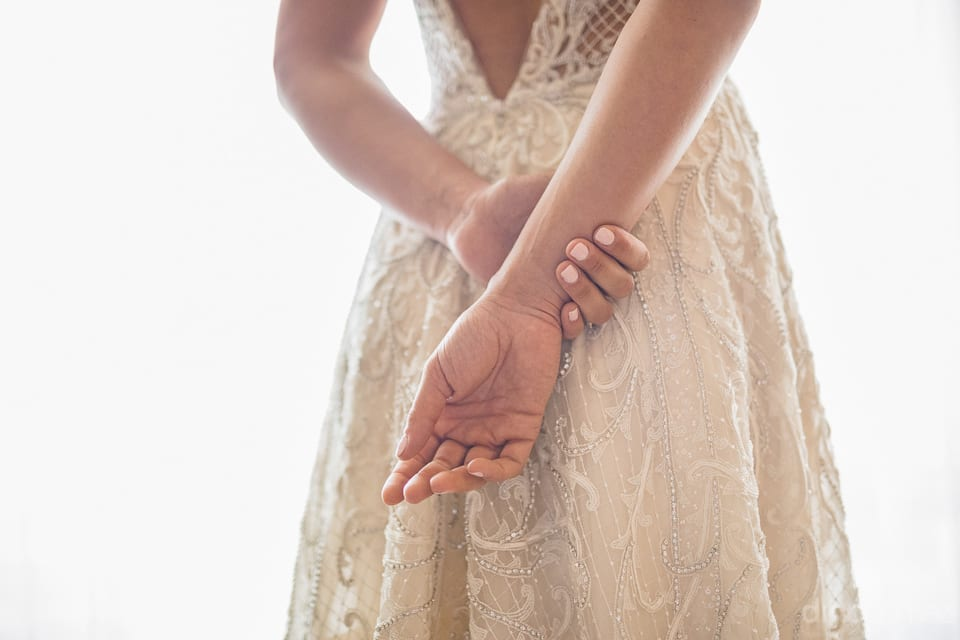 The image captures the beautiful hands of the bride at her back along with the etails of her wedding gown- Heather & Ross