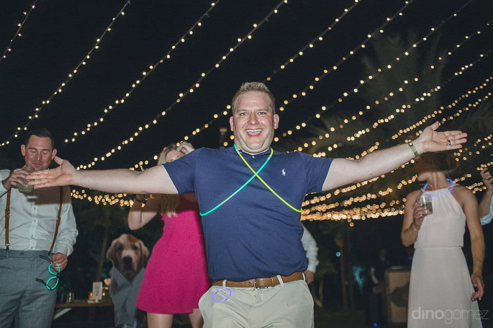 A handsome young guy is wearing the Glow bands around his chest and is posing for the camera at the evening party of the couple- Heather & Ross