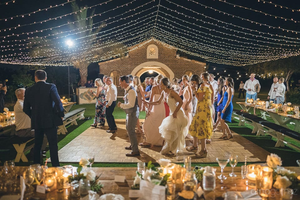Lovely bride is holding her wedding gown while dancing on the dance floor with the groom as well as other guets- Heather & Ross
