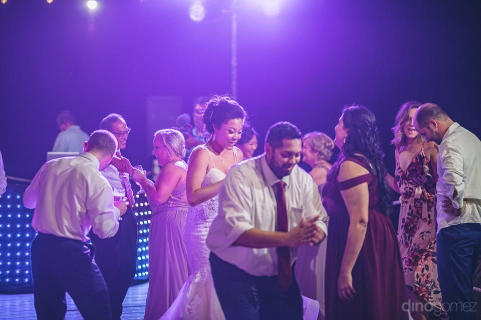 Lovely bride can be seen dancing with the friends under the beautiful colorful lights at the evening party-  Jay & Drew