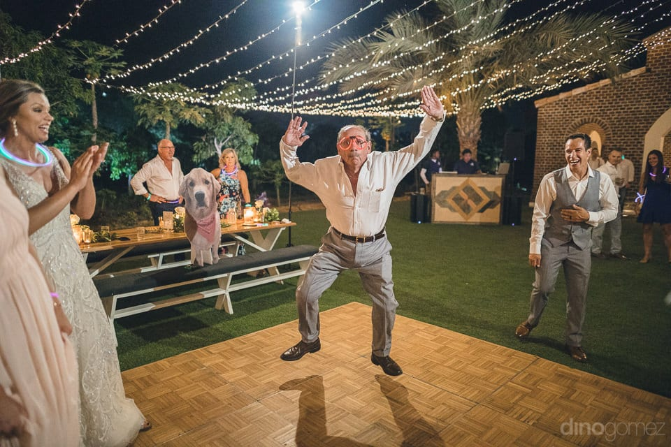 An elderly man is jumping in happiness on the dance floor at the wedding reception of the lovely couple- Heather & Ross