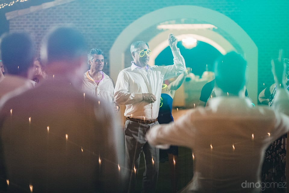 The picture beautifully captures a man dancing on the dance floor while wearing glasses made out of glow band at the evening party of the couple- Heather & Ross