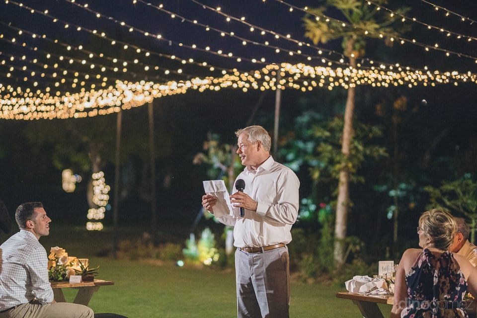 A gentleman is holding a piece of paper and reading it loud among the wedding guests at the evening party of the couple- Heather & Ross