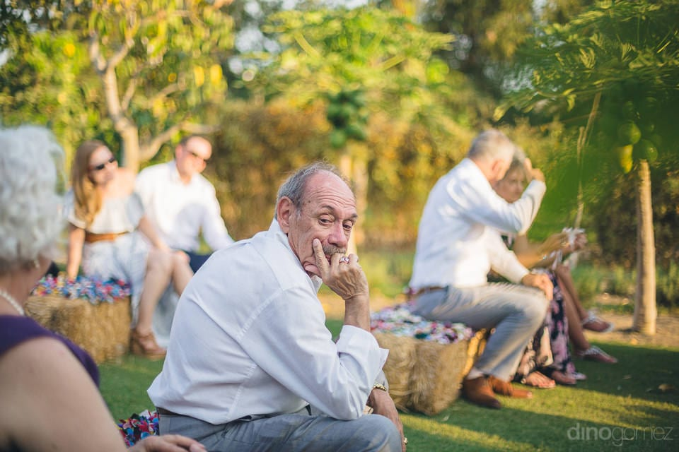 A gentleman is sitting on the seats made of hay grass and is thinking about something during the wedding ceremony of the couple- Heather & Ross