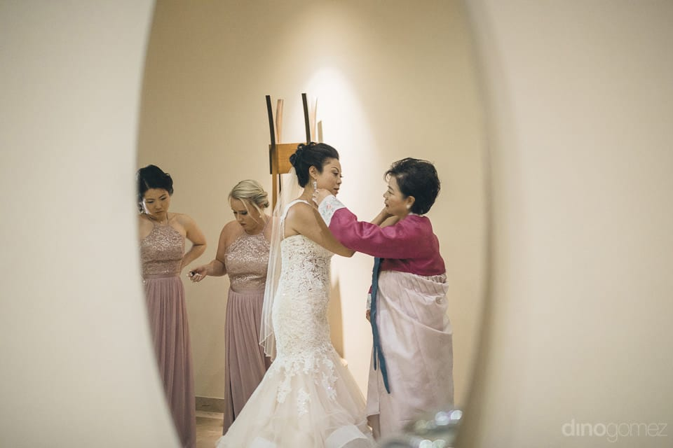 The bride is helping a lovely lady to get ready before leaving for the wedding stage inside the palace room- Jay & Drew