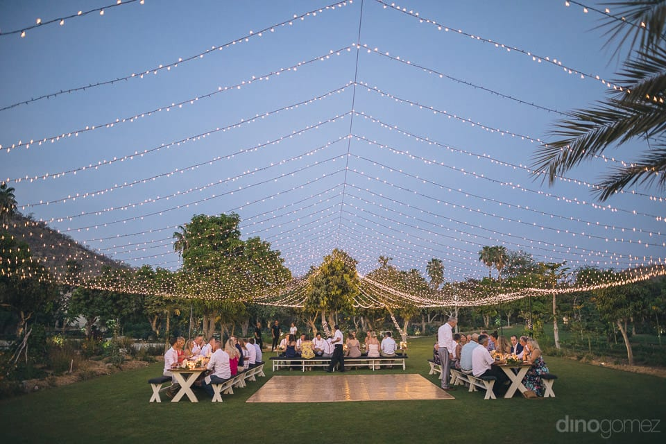 The picture captures beautiful net made out of the yellow lights for the evening party of the couple and guests sitting around the dinning table- Heather & Ross