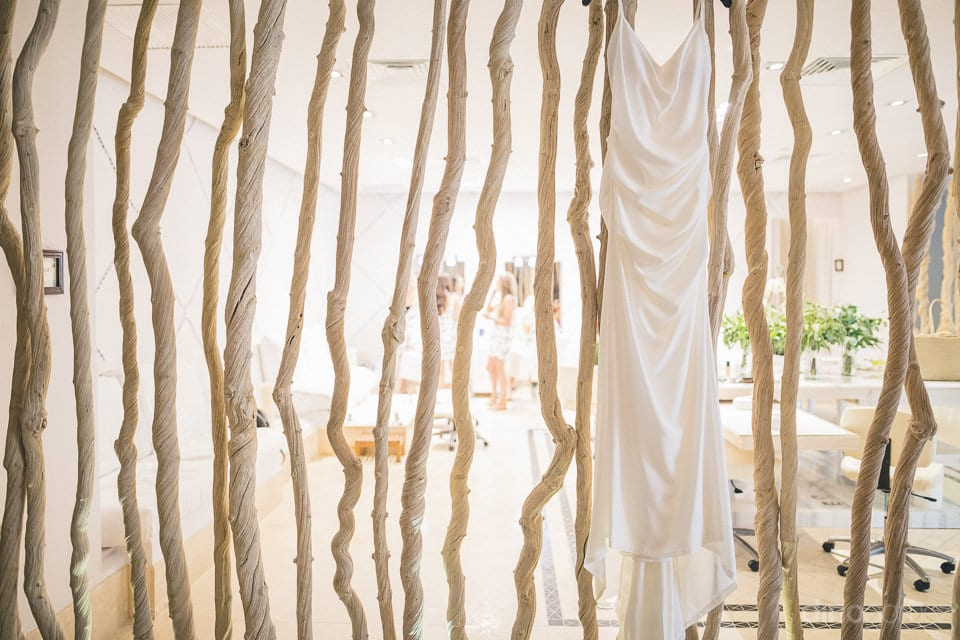 Beautiful silk white wedding gown of the bride is captured in the picture hanging on the wooden stand inside the room- Amber & Josh