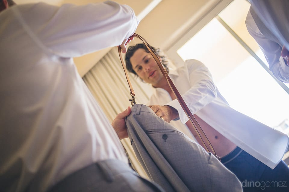 A pant with the hanging galace is held by a gentleman while getting ready for the wedding of lovely couple- Heather & Ross