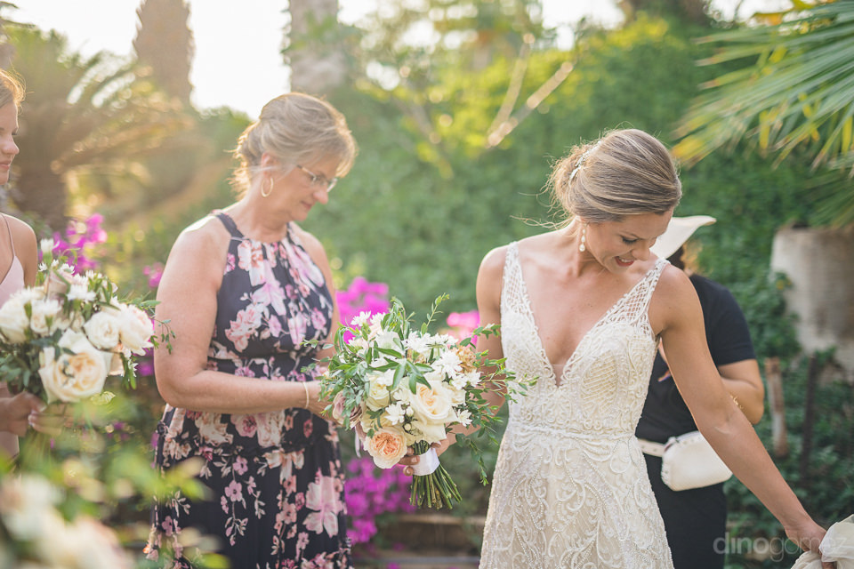 The lovely bride is holding a bouquet in her hands and is setting her wedding gown before walking towards the stage- Heather & Ross