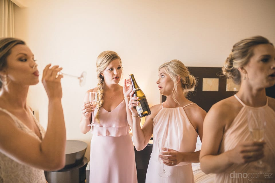 The bride along with her bridesmaid is standing inside the room of a palace and are raising a toast to the wedding- Heather & Ross