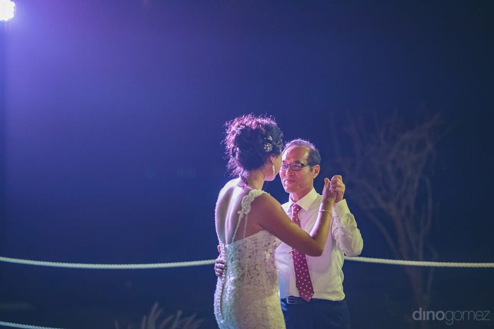 The lovely bride is holding the hands of a gentleman and is dancing with him at the reception party- Jay & Drew