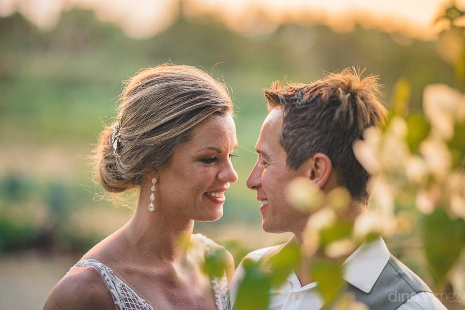 The couple is looking deep into each others eyes and admiring each other while standing in the beautiful farm- Heather & Ross