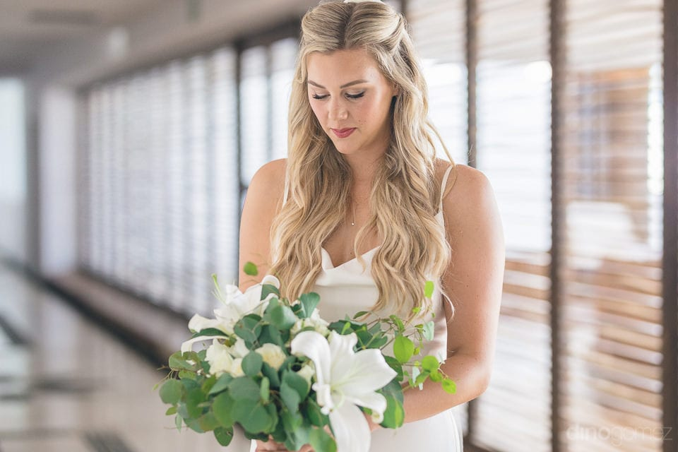 Lovely bride is looking at her wedding bouquet while posing for the camera- Amber & Josh
