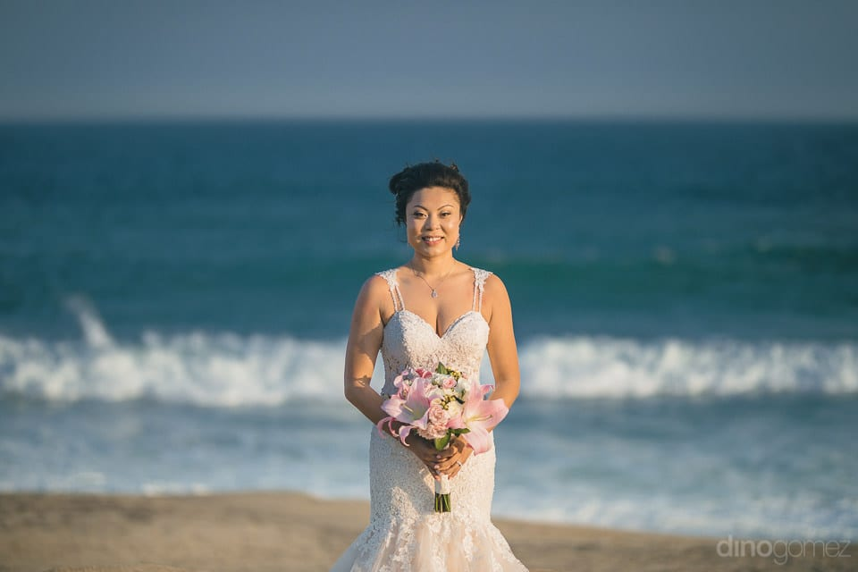 The bride is looking wonderful in her wedding dress & is posing beautifully near the sea- Jay & Drew