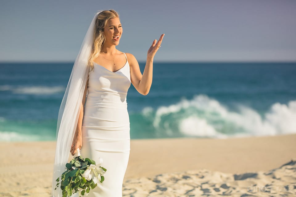 The bride is looking divine in her white wedding gown while standing at the beautiful beach- Amber & Josh