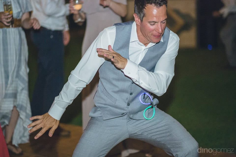 The groom is dancing to the beats of the music while wearing glasses made of flow sticks on his jacket's pocket- Heather & Ross