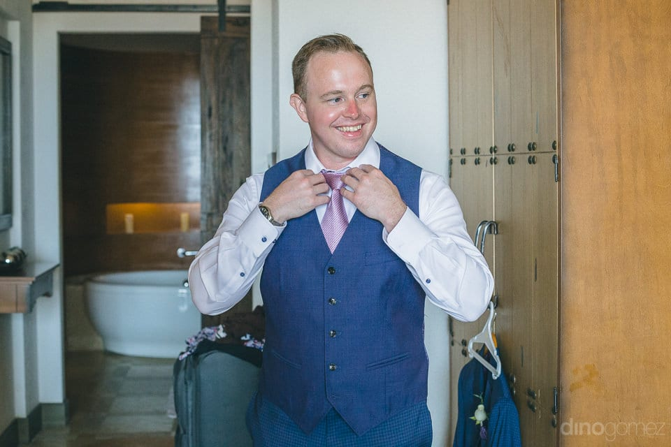 Handsome groom is setting his tie and smiling brightly while doing the settings- Jay & Drew