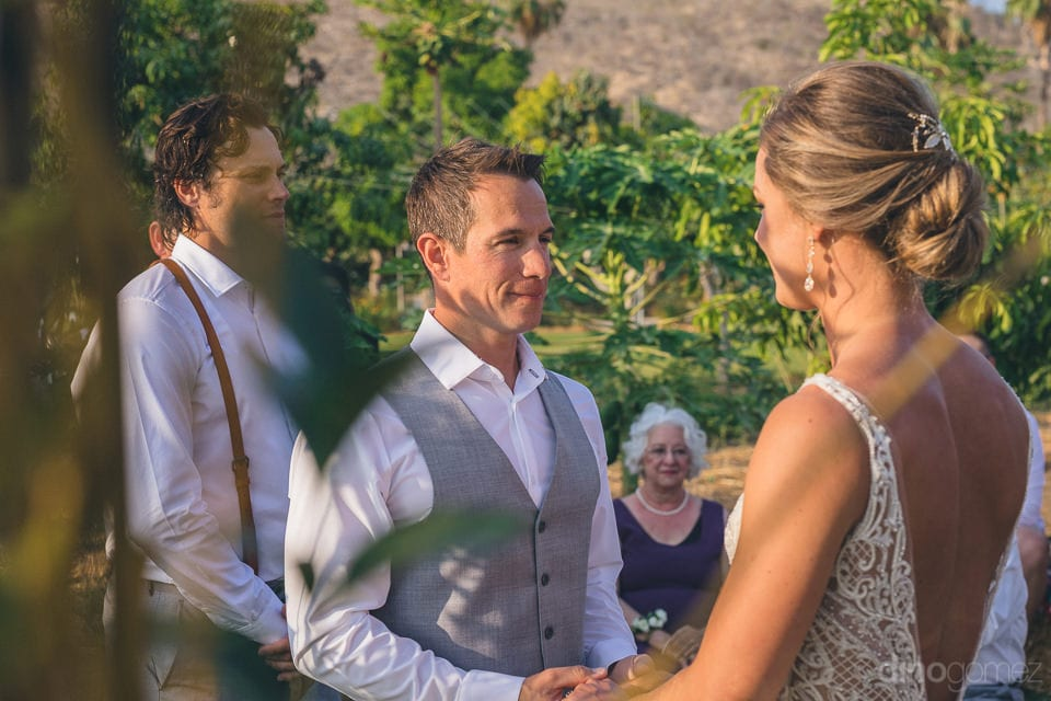 Handsome groom is looking into the eyes of the bride during the wedding ceremonies of the couple- Heather & Ross