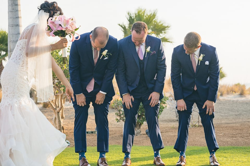 The handsome groom is standing among his friends and are looking at their matching socks- Jay & Drew