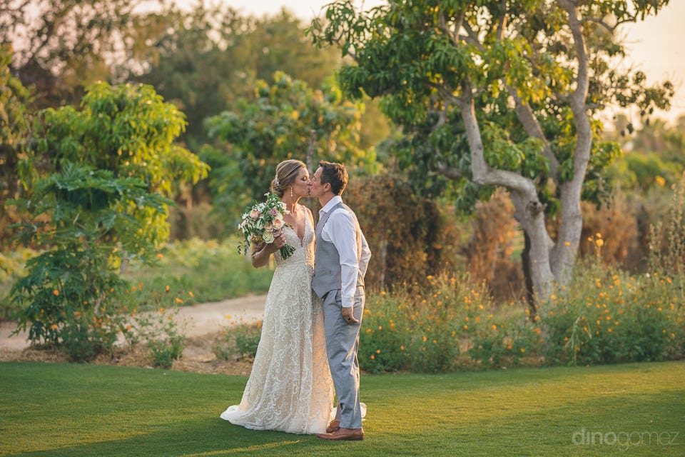 Beautiful newly married couple is standing in the graden among green plants and is kissing each other- Heather & Ross