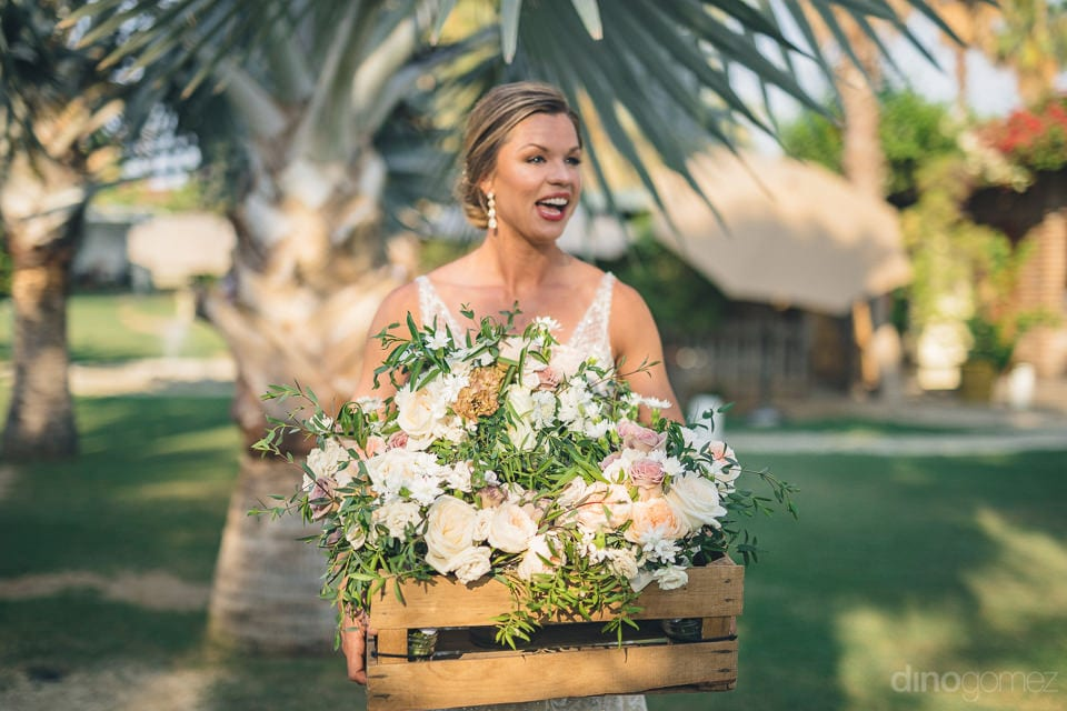 Gorgeous bride is holding a crate full of bouquet to distribute among the bridesmaids at her wedding- Heather & Ross