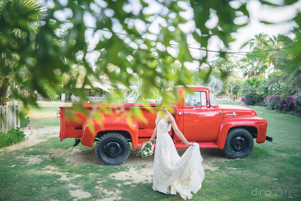 The bride is giving a lovely pose infront a vintage car painted in bold red color- Heather & Ross