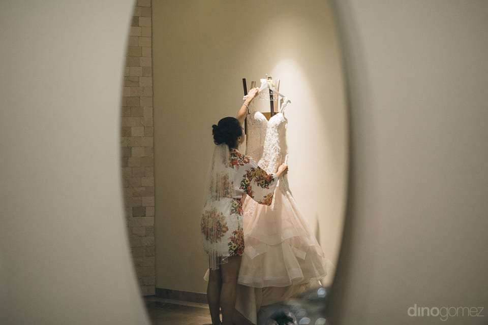 Lovely bride is looking at her wedding dress hung on a beautifull wall- Jay & Drew