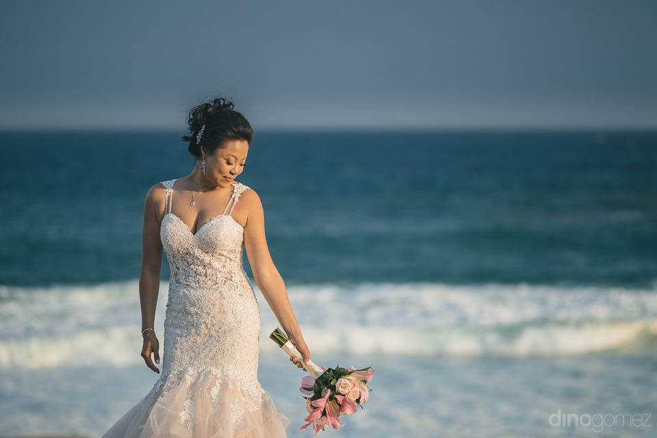 The bride is looking gorgeous while posing for the camera standing infront of the sea- Jay & Drew