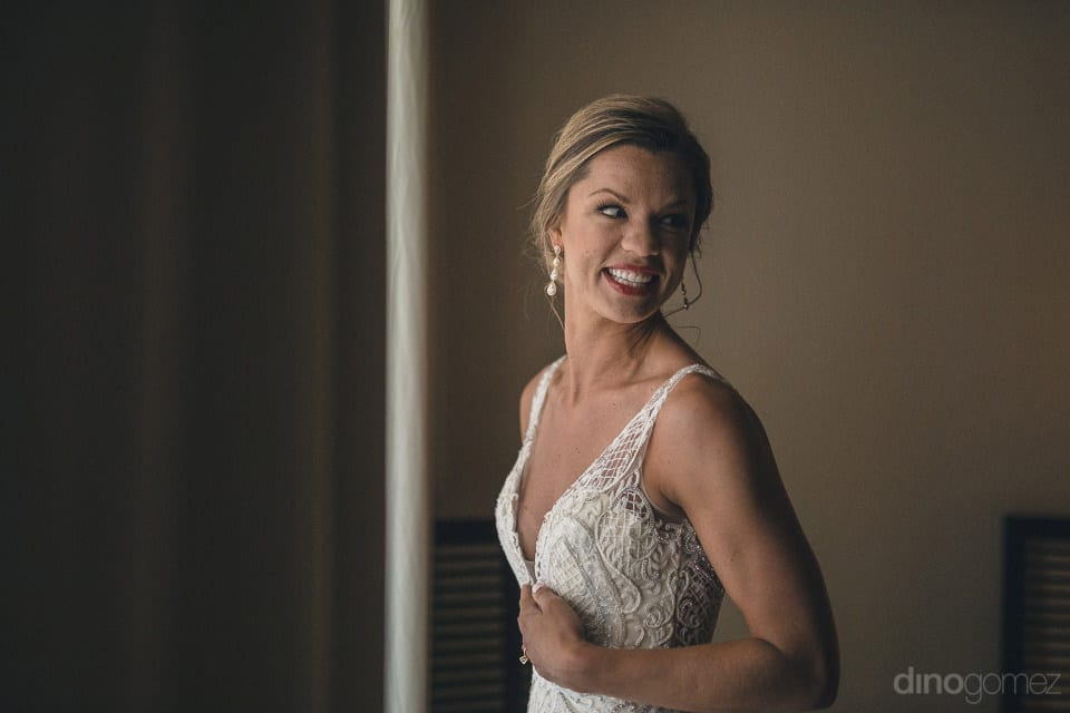 The bride is dressed in beautiful white wedding gown and is smiling away from the camera to give a beautiful pose- Heather & Ross