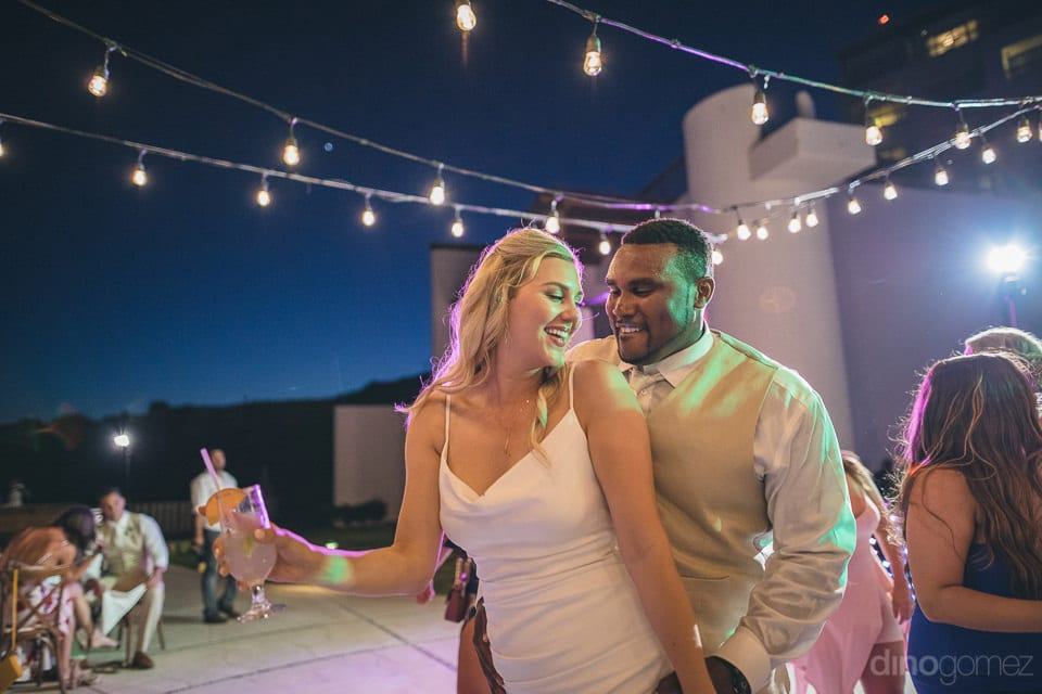 Gorgeous newly married coupke is dancing on the dance floor while the bride is holding a glass of drink in her hands- Amber & Josh
