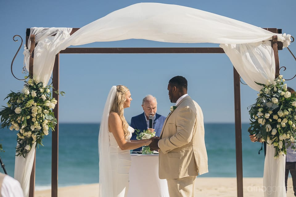 The couple is holding each others hands while taking the wedding oath at the beach side- Amber & Josh